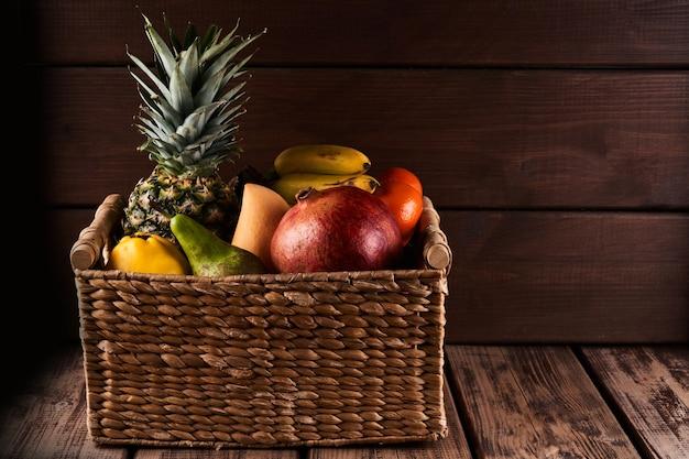 나무 배경에 바구니에 신선한 육즙 다채로운 이국적인 열대 과일의 혼합