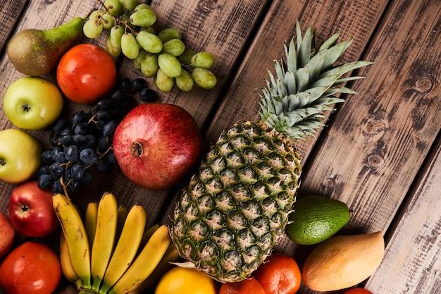 나무 배경 상단 보기에 신선하고 육즙이 많은 다채로운 이국적인 열대 과일의 혼합