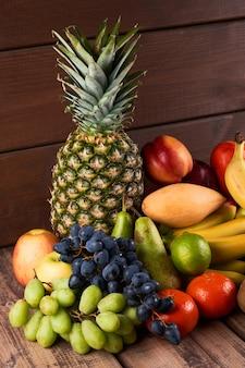 나무 배경에 신선하고 즙이 많은 다채로운 이국적인 열대 과일의 혼합