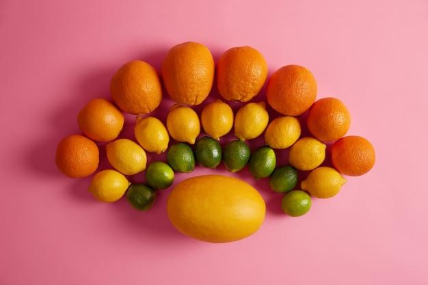 黄色いメロンの周りに半円状に配置された新鮮な熟した柑橘系の果物のミックス。ビタミンや栄養素が豊富なローフード。フルーツの品揃え。上面図とフラットレイ。健康的な食事、収穫、ダイエットの概念 無料写真