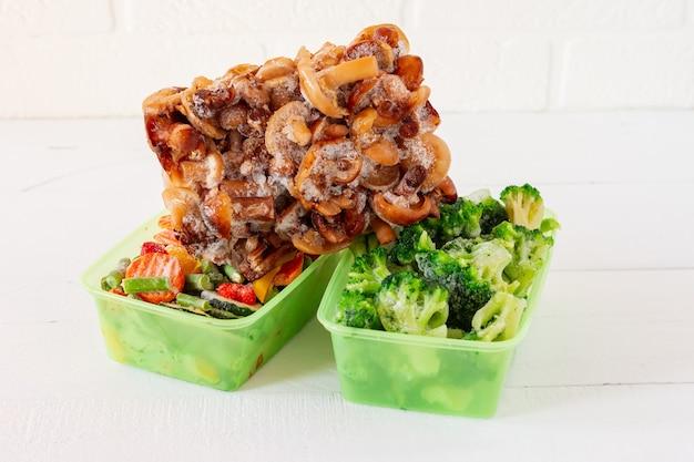 Смесь замороженных овощей и грибов в пластиковых контейнерах для хранения. запасы еды на зиму.