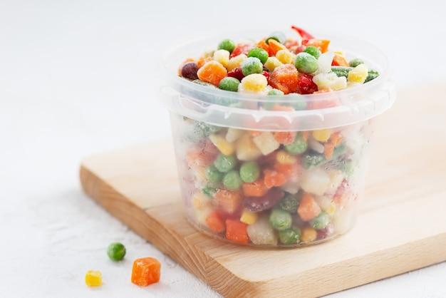 Смесь замороженных овощей в контейнере на деревянной доске