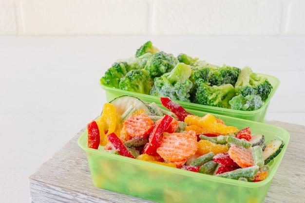 Смесь замороженных овощей в пластиковых контейнерах для хранения. запасы еды на зиму.