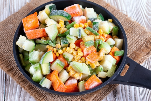 鍋に冷凍野菜を混ぜる。スタジオ写真