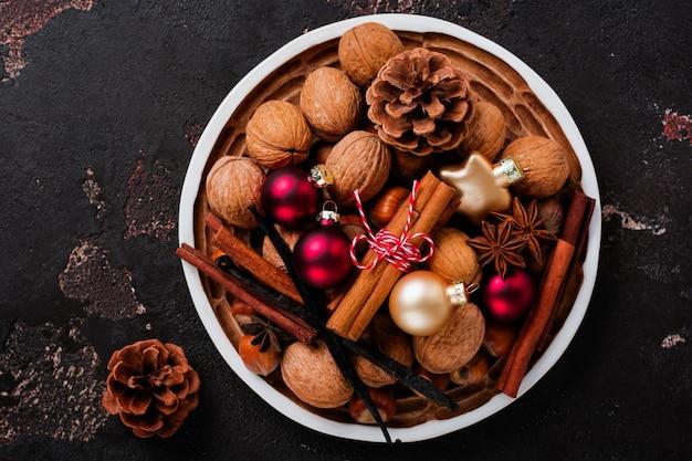 Смесь здоровых сырых лесных и грецких орехов, палочек корицы, аниса, ванили, шоколада и рождественских игрушек в керамической тарелке на коричневой бетонной поверхности