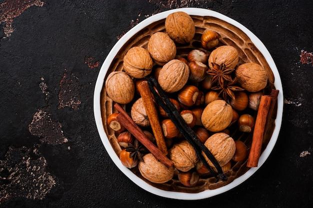 Смесь здоровых сырых лесных и грецких орехов, палочек корицы, аниса, ванили в керамической тарелке на коричневой бетонной поверхности.