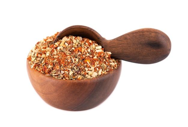 木製のボウルとスプーンにハーブ、スパイス、ドライトマトを混ぜる
