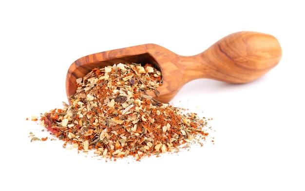 ハーブ、スパイス、ドライトマトを木製のスクープに混ぜ、白で隔離