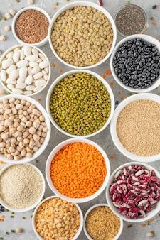 Смесь бобовых, нута, чечевицы, фасоли, гороха, киноа, кунжута, чиа, семян льна в мисках на сером фоне бетона. здоровая, веганская и безглютеновая еда. вид сверху.