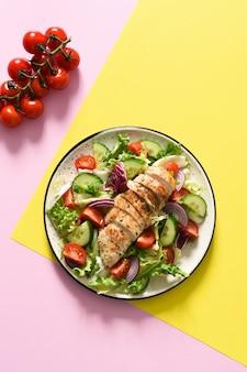 Смесь салата, помидоров и куриного филе гриль на желто-розовой поверхности. салат на цветной поверхности. продовольственный тренд.