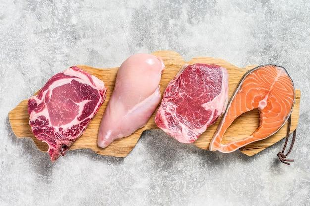 Смесь мясных сырых стейков лосося, говядины, свинины и курицы. серый фон. вид сверху.