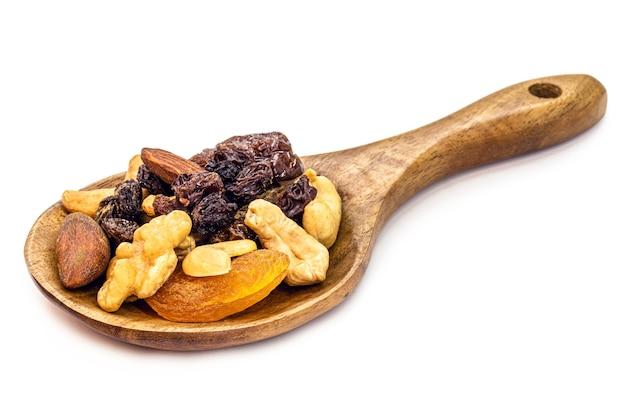 소박한 나무 숟가락에 견과류와 탈수 과일을 섞습니다. 브라질 너트, 살구, 건포도, 자두 및 호두