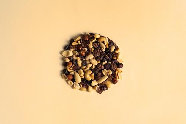 견과류와 말린 과일을 섞어 노란색 배경에 원을 형성합니다. 건포도, 말린 매자나무, 헤이즐넛, 땅콩, 아몬드.