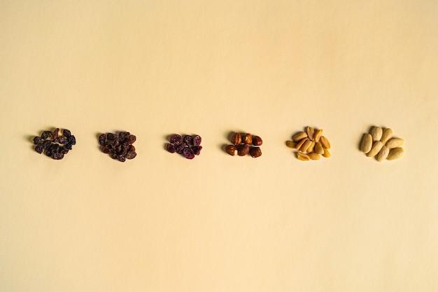 견과류와 말린 과일을 노란색 배경에 종류와 색상별로 혼합합니다. 건포도, 말린 매자나무, 헤이즐넛, 땅콩, 아몬드.