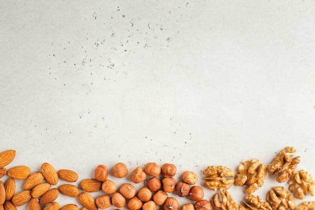 Смесь орехов. каркас из миндаля, фундука и грецких орехов. здоровые закуски, вегетарианство. скопируйте пространство.
