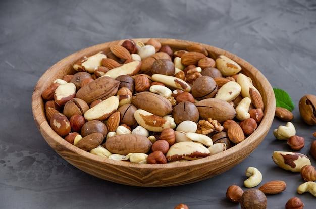 Смесь орехов в деревянной миске на темном фоне бетона. концепция здорового питания. горизонтальный, выборочный фокус.