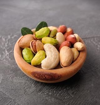 Смесь орехов в деревянной тарелке на бетонном столе. арахис, кешью, фистки