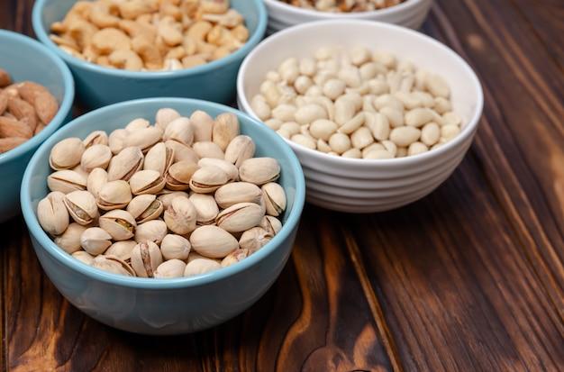 Смесь орехов на столе. грецкие орехи, миндаль, фисташки, кешью, арахис