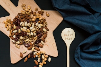 Mix of nuts on cutting board near wood spoon