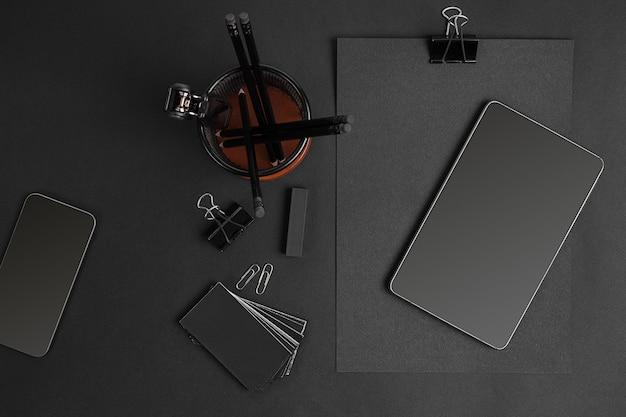 現代のオフィスの机の上の事務用品とビジネスガジェットのミックス。黒の背景に黒のオブジェクト。