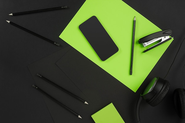 近代的なオフィスの机の上の事務用品のミックス。黒の背景に黒のオブジェクト。