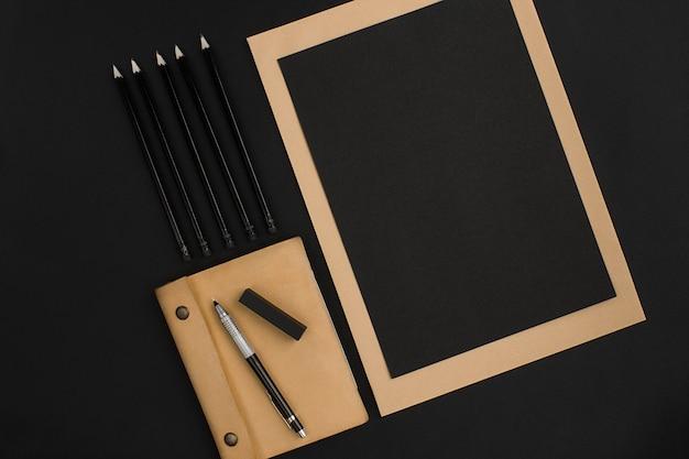 Смесь канцелярских товаров на современном офисном столе. объект на черном фоне. вид сверху. натюрморт. копировать пространство