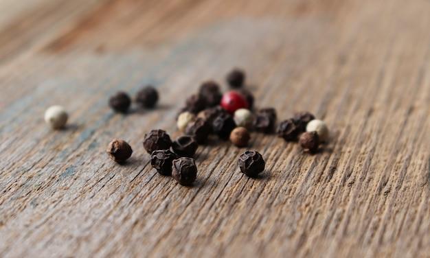 古いテーブルのクローズアップで、木製の背景にペッパーコーンソンのミックス。種子の赤、黒、緑、白のドライペッパー。食品のコンセプト。