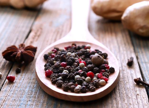 木のスプーンペッパーコーンソンのミックス赤黒緑と白の乾燥コショウの種食品の概念