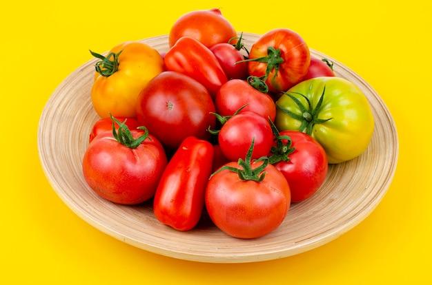 Смесь спелых красочных помидоров на ярко-желтом фоне. студийное фото.