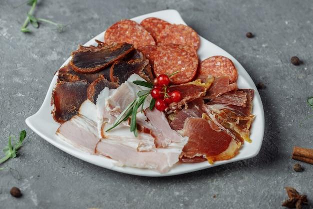 Смесь нарезанного мяса на белой тарелке.
