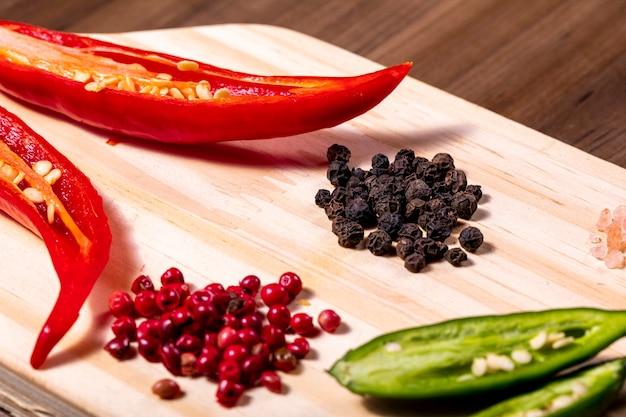향신료, 빨강 및 검정 후추 곡물, 핑크 히말라야 소금 및 체리 토마토가 들어있는 나무 상자를 혼합합니다.