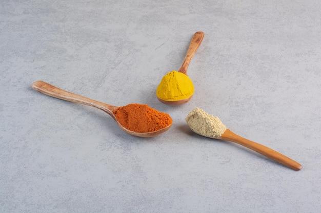 콘크리트 배경에 있는 나무 숟가락에 향신료를 섞으세요.