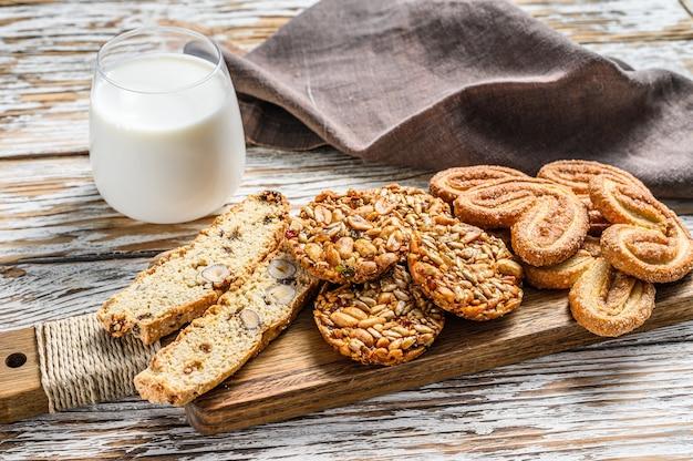 달콤한 쿠키와 우유 한 잔을 섞습니다. 흰색 나무 테이블. 평면도.