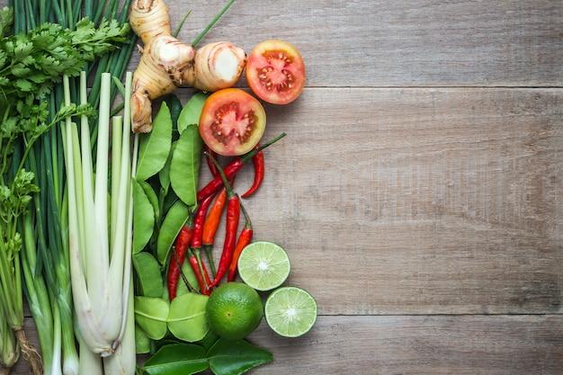 木製の背景に竹トレイでタイの野菜のミックス。