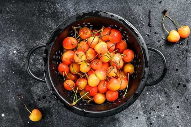 ザルに黄色と赤の熟したサクランボを混ぜます。