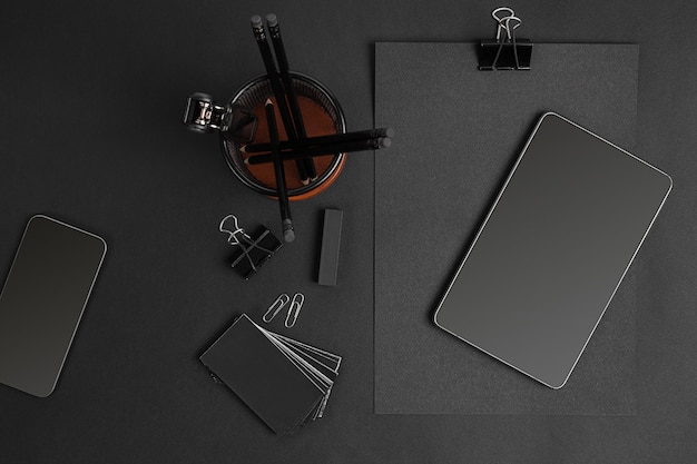 Mix of office supplies and business gadgets on a modern office desk. black object on a black background.