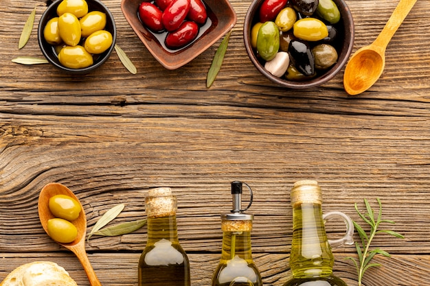 Mix of olives in bowls and oil bottles
