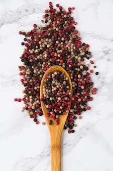 Mix of a pepper spice grains in a wooden spoon