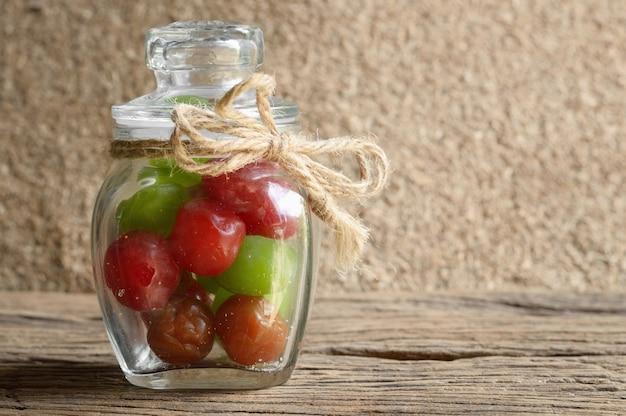 木製のテーブルにガラス瓶でミックスピクルチェリーフルーツ
