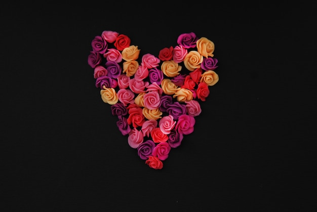Mix of pink fake roses flowers heart shaped, black copy space.