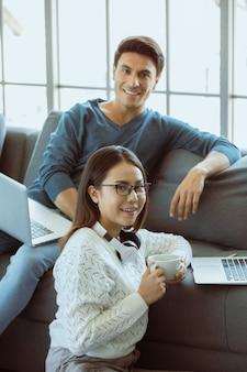 Семейные любители смешанной расы, кавказский муж и азиатская жена, сидят в гостиной и работают через портативный компьютер на диване в простых расслабляющих жестах. концепция работы дома и новый нормальный современный образ жизни.