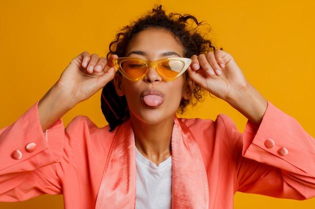 黄色の背景の上に舌を見せてしかめっ面をする人種の女性を混ぜます。スタジオ撮影。