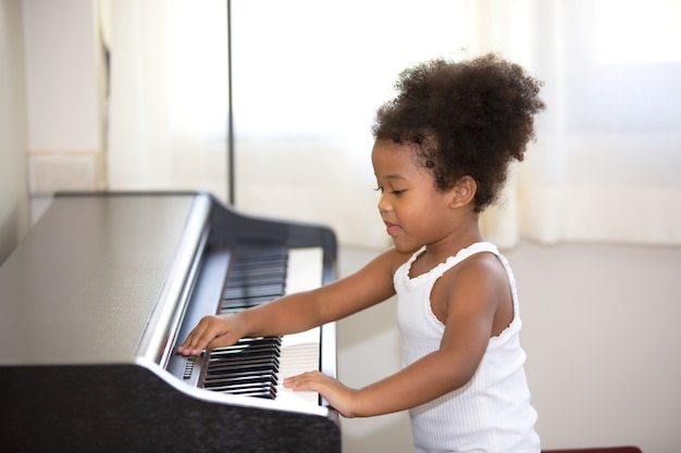 Mix race kid practice to play piano in house