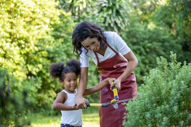 庭でレースのお母さんと小さな女の子の挿し木植物を混ぜます。