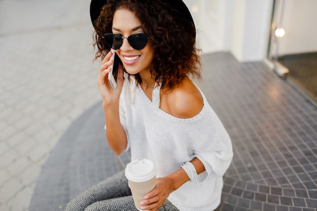 Mix race woman, blogger or store manager  talking by mobile phone during coffee break. sitting on stairs and holding paper cup of hot beverage. white and black  fashion outfit.