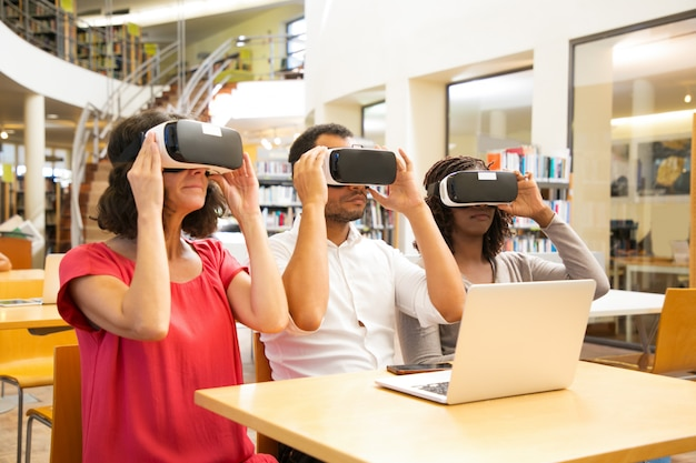 Mix raced team of adult students wearing vr goggles