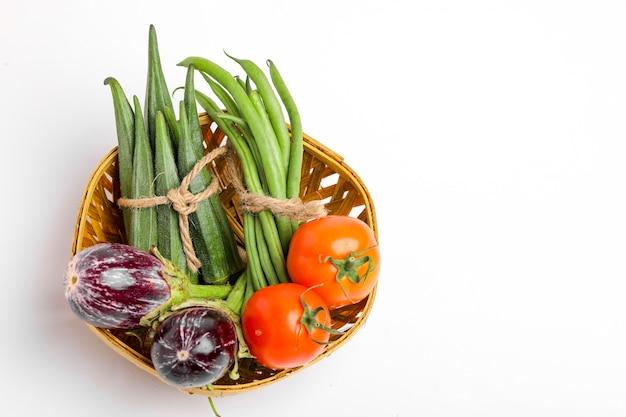 Смешайте сырые овощи в деревянной миске на белом фоне