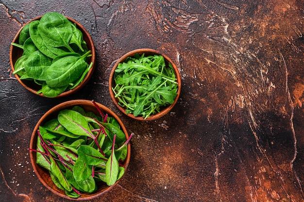 Смешайте салатные листья, рукколу, шпинат и свиный мангольд в деревянных мисках.