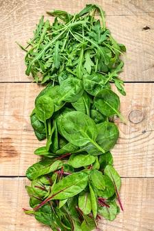 Смешайте салатные листья, рукколу, шпинат и свиный мангольд