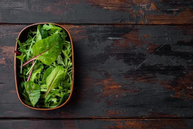 Смешайте салатные листья, швейцарский мангольд и рукколу на фоне старого темного деревянного стола, плоская планировка, вид сверху, с местом для текста